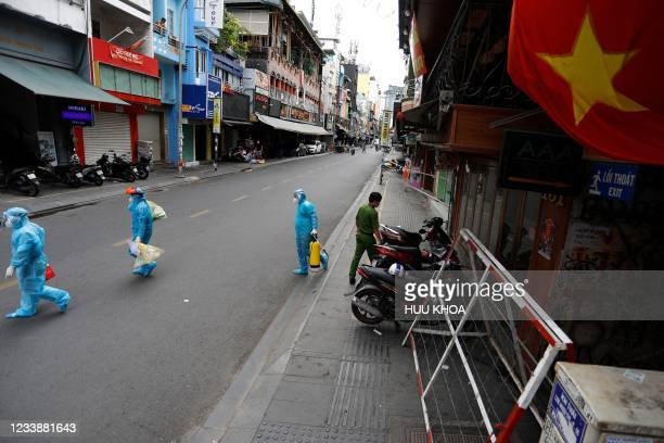 Medical workers collecting test samples from residents walk past in Ho Chi Minh City on July 9 on the first day of the government imposed two-week...