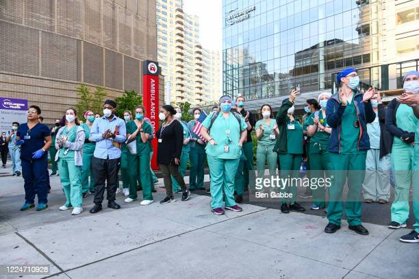 Medical workers come out for the 7pm cheer in front of the NYU Langone Medical Center during the COVID19 pandemic on May 13 2020 in New York City...