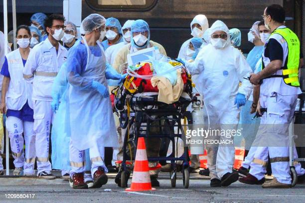 Medical workers disembark a patient infected with the COVID-19 out of a medicalised TGV high speed train after it arrived on April 10, 2020 at...