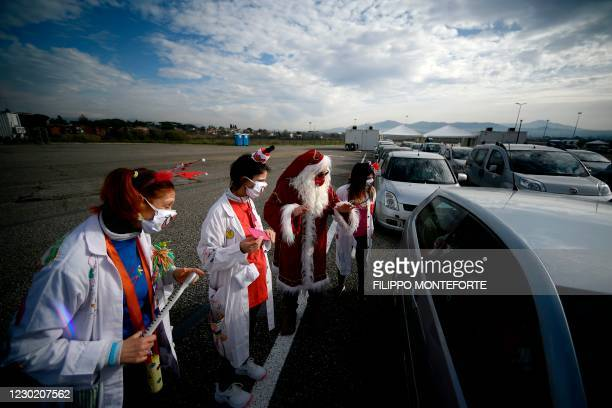 Medical workers dressed as clowns and Santa Claus entertain people lined up in their car to undergo a COVID-19 swab test for coronavirus, on December...