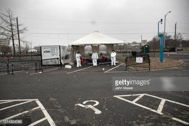 Medical workers dressed in personal protective equipment await new patients a drive-thru coronavirus testing station at Cummings Park on March 23,...