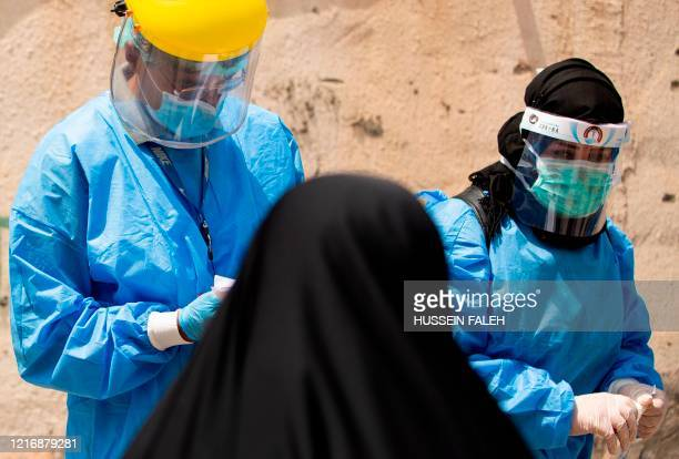 Medical workers dressed in PPE prepare to take swabs from subjects being tested for COVID-19 coronavirus disease, in the 5-Miles district of Iraq's...