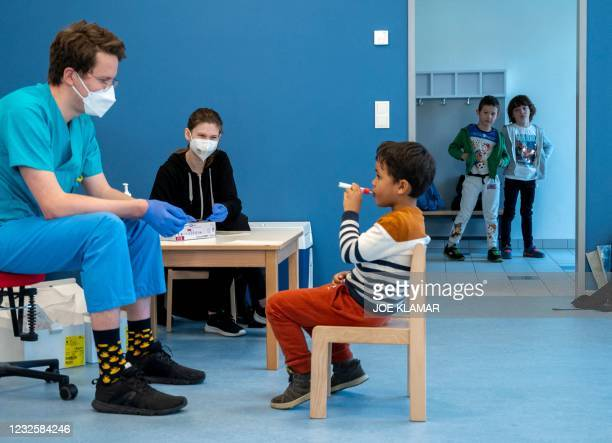 Medical workers follow as pre-school boy uses a newly developed, lollipop-shaped Covid-19 test prior to the testing of pre-schoolers at the 'City of...