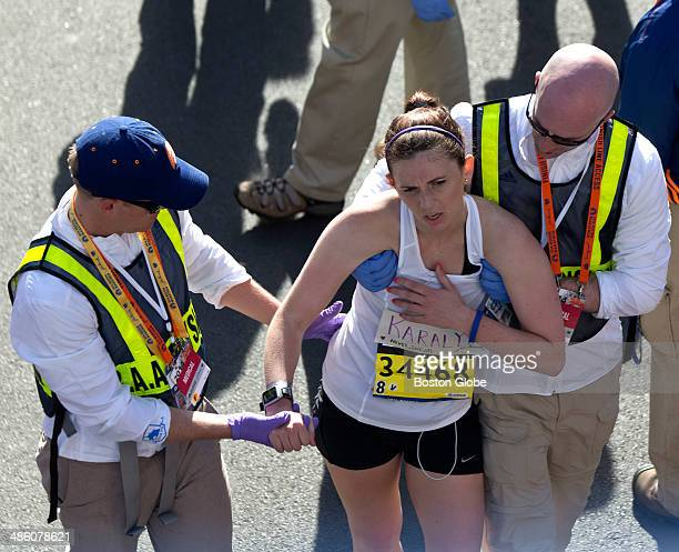 Medical workers help exhausted runner Karalyn Spadaro at the finish line of the 118th Boston Marathon on Monday April 21 2014
