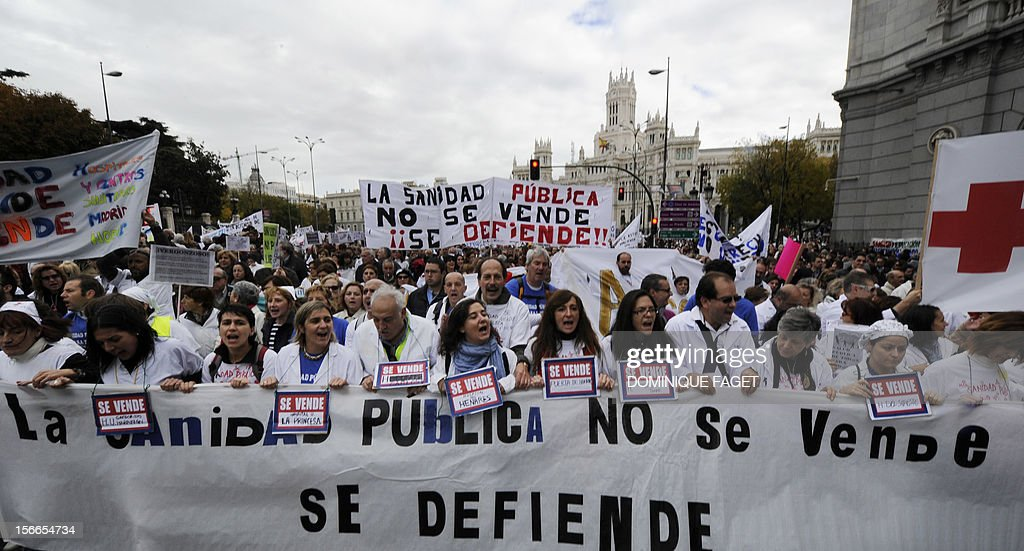 Medical workers hold a placard reading 'Health public services are not on sale' during a demonstration against the Spanish government's latest austerity measures in the center of Madrid on November 18, 2012. Thousands of medical workers gathered in Madrid to express their anger against the austerity measures.