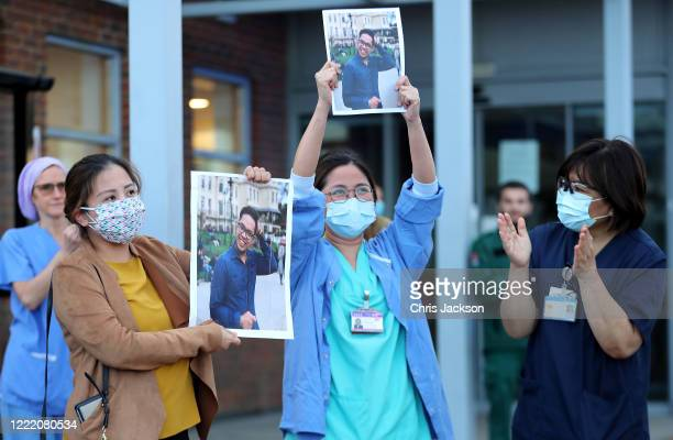 Medical workers hold up pictures of their friend and colleague Ken Lambatan who died of COVID19 as they 'Clap for Our Carers' outside Kingston...