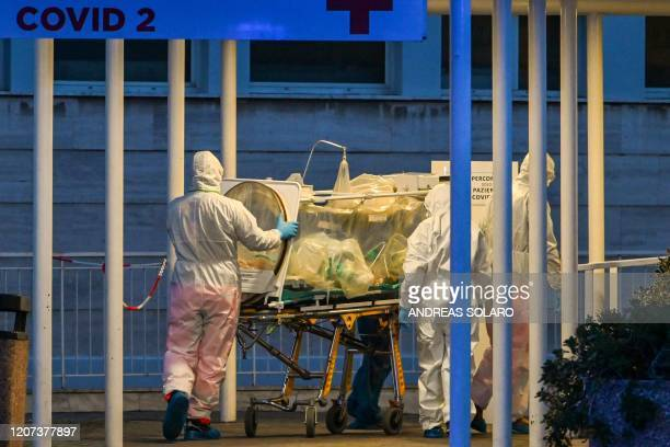 Medical workers in overalls stretch a patient under intensive care into the newly built Columbus Covid 2 temporary hospital to fight the new...