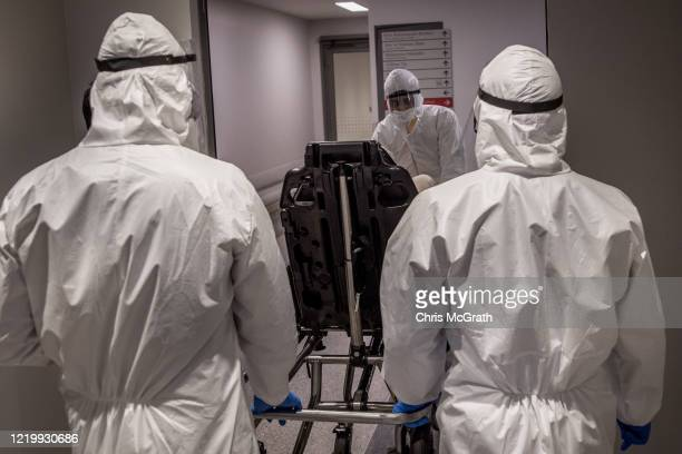 Medical workers in personal protective equipment wheel a patient suspected of having the COVID19 virus through to the emergency ward at the Acibadem...