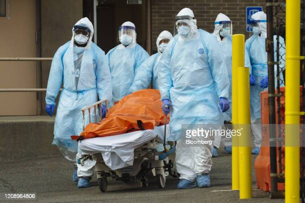 Medical workers in protective clothing move the body of a deceased patient to a refrigerated overflow morgue outside the Wyckoff Heights Medical...