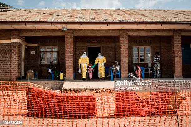 TOPSHOT Medical workers lead a young girl with suspected Ebola into the unconfirmed Ebola patients ward run by The Alliance for International Medical...