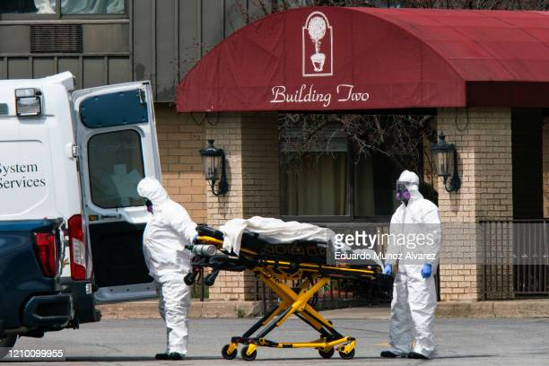 Medical workers load a deceased body into an ambulance while wearing masks and personal protective equipment at Andover Subacute and Rehabilitation...