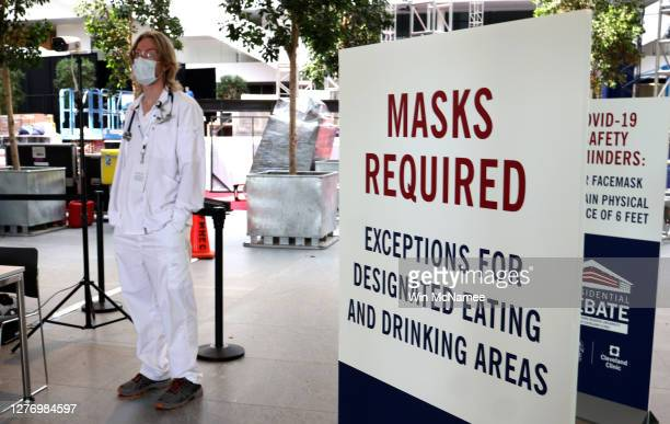 Medical workers monitor the body temperatures of workers preparing for the first presidential debate between US President Donald Trump and Democratic...