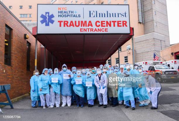 Medical workers pose for a photo with thank you signs outside Elmhurst Hospital Center Emergency Room during the coronavirus pandemic on April 20...