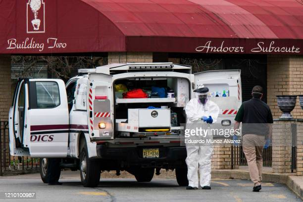 Medical workers put on masks and personal protective equipment while preparing to transport a deceased body at Andover Subacute and Rehabilitation...