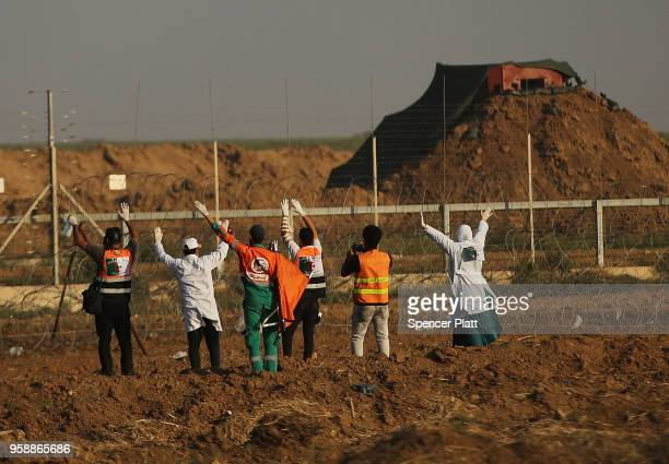 Medical workers raise there hands as they approach the border fence with Israel to retrieve protesters caught in the fence on May 15 2018 in Gaza...