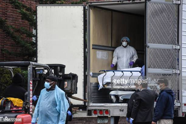 Medical workers remove a body from a refrigerated truck outside of the Brooklyn Hospital on March 31, 2020 in New York City. Due to a surge in deaths...