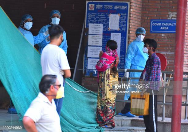 Medical workers speak with family members of people admitted with coronavirus infections, outside the Covid-19 ward at Lok Nayak Jai Prakash Narayan...