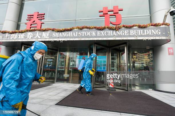 Medical workers spray antiseptic outside of the main gate of Shanghai Stock Exchange Building on February 03 2020 in Shanghai China