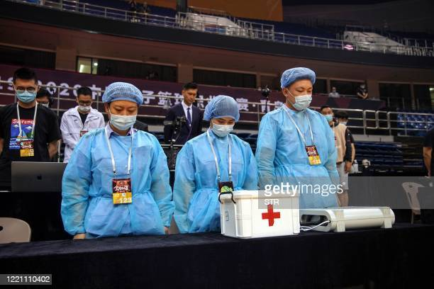 Medical workers stand in a silent tribute for victims of the COVID-19 coronavirus before the CBA basketball match between Nanjing Monkey Kings and...