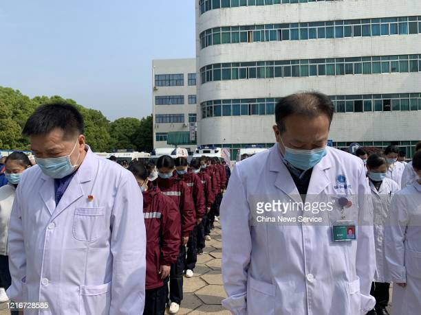 Medical workers stand in silent tribute at Wuhan Union Hospital during a three minute national memorial to mourn martyrs who died in the fight...