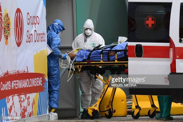 TOPSHOT Medical workers stretch a patient from an Italian Red Cross ambulance into an intensive care unit set up in a sports center outside the San...