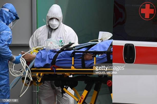 Medical workers stretch a patient from an Italian Red Cross ambulance into an intensive care unit set up in a sports center outside the San Raffaele...