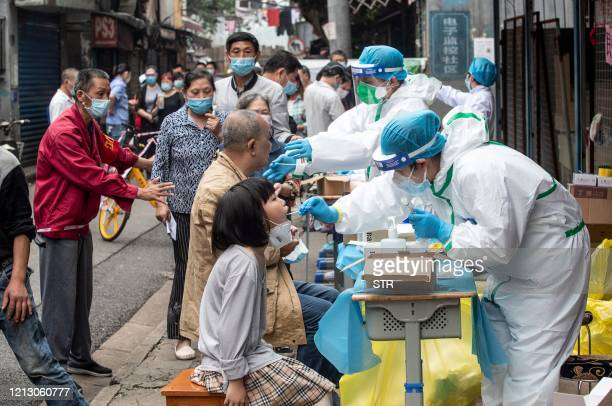 Medical workers take swab samples from residents to be tested for the COVID-19 coronavirus, in a street in Wuhan in China's central Hubei province on...