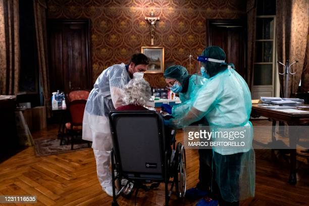 Medical workers tend to an elderly woman receiving an injection of the Pfizer-BioNTech Covid-19 vaccine on February 12, 2021 at the Tapparelli...