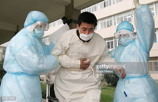 Medical workers transfer a patient during a medical drill to deal with a Severe Acute Respiratory Syndrome at a hospital December 18, 2004 in...