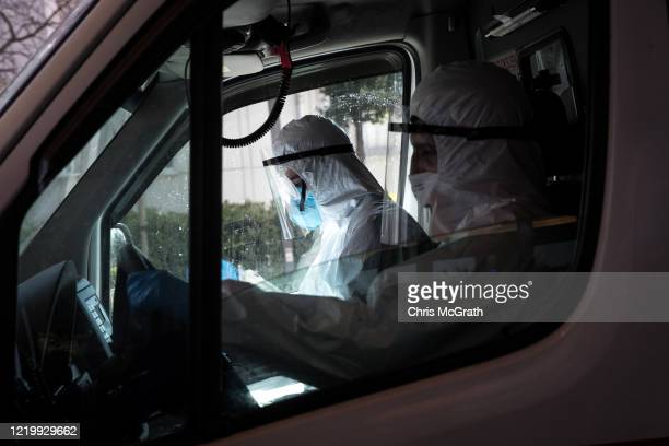 Medical workers wait in an ambulance after dropping off a patient suspected of having the COVID19 virus outside the emergency entrance at the...