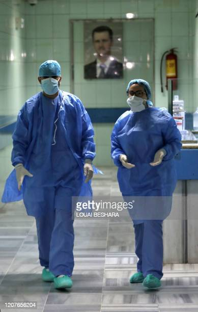 Medical workers walk in the hall of a ward at a hospital in the Syrian capital Damascus , on March 19 being prepared to quarantine possible cases of...
