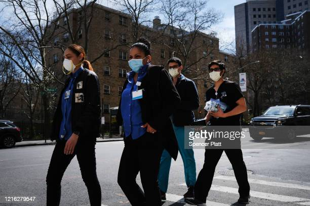 Medical workers walk outside of Mount Sinai Hospital amid the coronavirus pandemic on April 01 2020 in New York City Hospitals in New York City the...