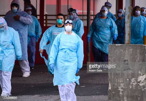 Medical workers walk outside the Elmhurst Hospital Center Emergency Room during the coronavirus pandemic on April 20 2020 in New York City COVID19...