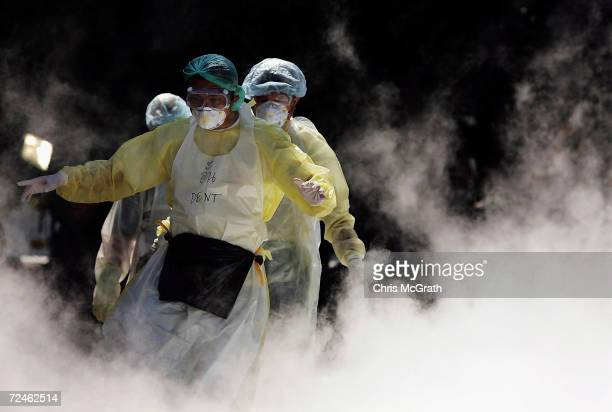 Medical workers walk through dry ice vapour at a makeshift morgue inside a Buddhist temple on January 2 2005 in Takuapa Thailand The bloated and...