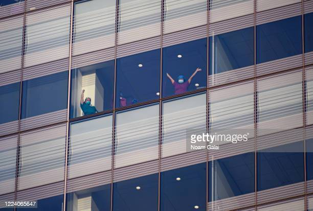 Medical workers wave from the window at NYU Langone Health hospital as people applaud to show their gratitude to medical staff and essential workers...