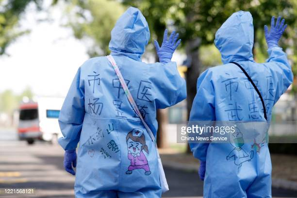 Medical workers wave goodbye as the last two COVID19 patients are discharged from Xiaotangshan Hospital on April 28 2020 in Beijing China All COVID19...