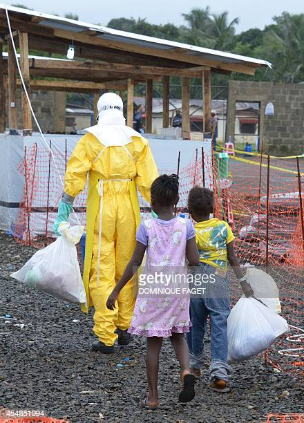 Medical workers wearing Personal Protective Equipment leads Ebola infected children in the high-risk area of the Elwa hospital runned by Medecins...