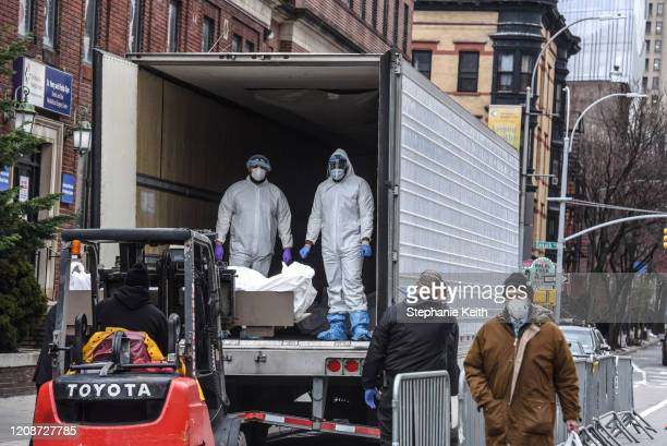 Medical workers wearing personal protective gear remove a body from a refrigerator truck outside of the Brooklyn Hospital on March 31, 2020 in New...