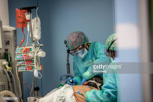 Medical workers wearing protective face masks goggles and scrubs tend to a patient on a ventilator diagnosed with Covid19 on the intensive care unit...