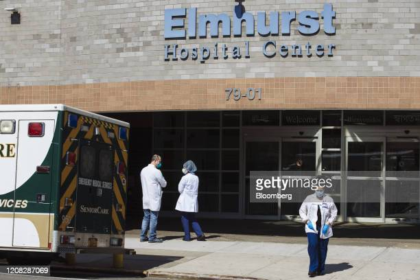 Medical workers wearing protective masks and gloves stand outside the Elmhurst Hospital Center in the Queens borough of New York US on Thursday March...