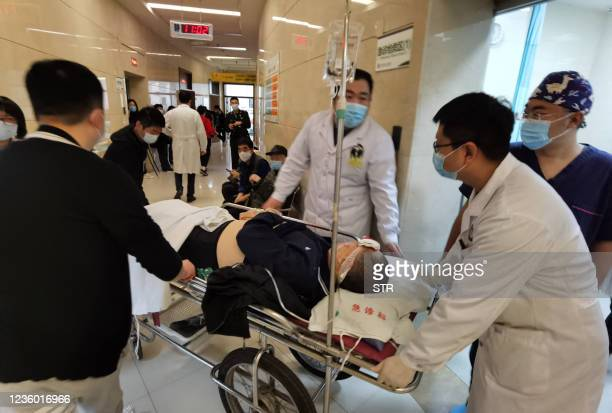 Medical workers wheel a patient at a hospital in Shenyang, China's northeastern Liaoning province on October 21 after a gas explosion at a restaurant...