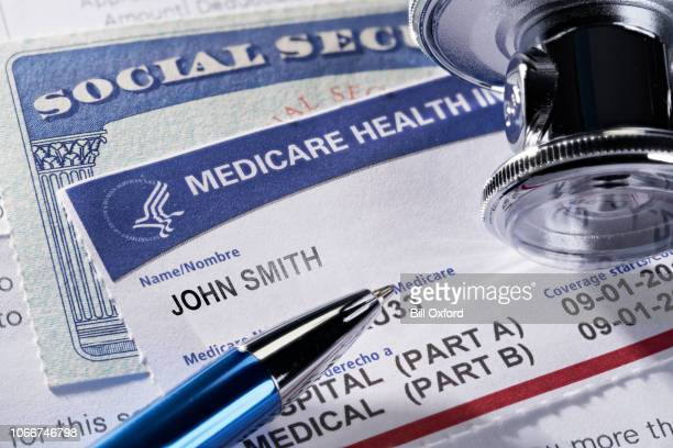 medicare health insurance and social security card on medical report and stethoscope - medical insurance stock pictures, royalty-free photos & images