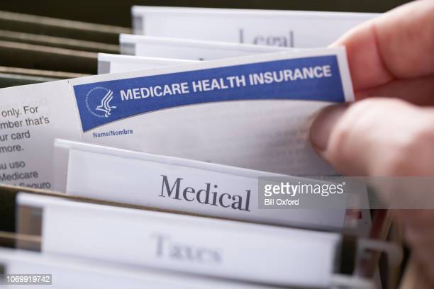medicare health insurance card in file folder - health insurance stock pictures, royalty-free photos & images