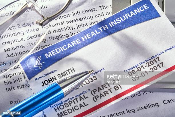 medicare health insurance card on medical report docuement - medicare stock pictures, royalty-free photos & images