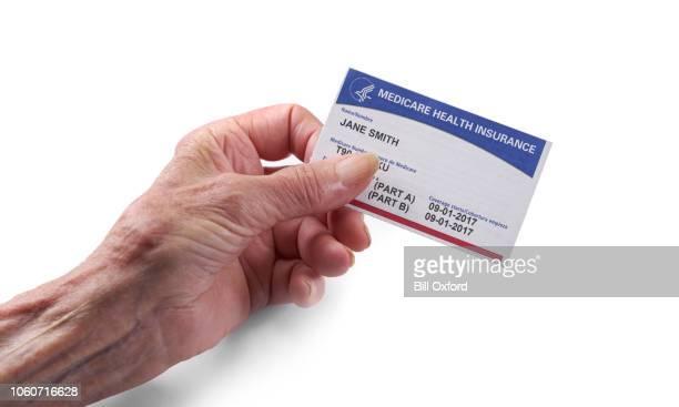 medicare ziekteverzekeringskaart: vrouw met nieuwe kaart met witte achtergrond in de hand - medicare stockfoto's en -beelden