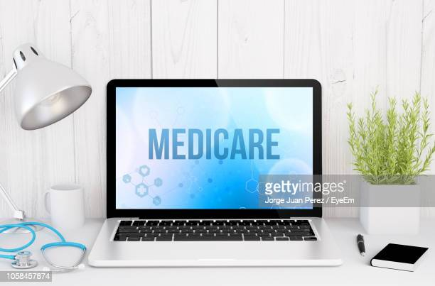 medicare text on laptop screen at table - medicare stock pictures, royalty-free photos & images