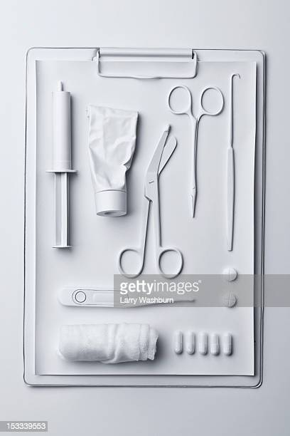 Medicine and medical equipment painted white and laid out on a clipboard