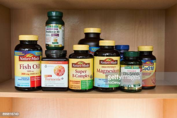 medicine cabinet shelf with variety of vitamins and nutritional supplements - nutritional supplement stock pictures, royalty-free photos & images