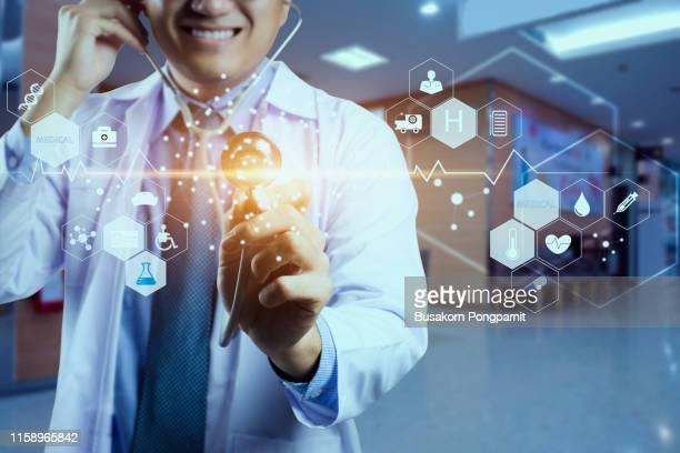 medicine doctor and stethoscope in hand touching icon medical network connection with modern virtual screen interface, medical technology network concept - sinal de emergência informação imagens e fotografias de stock