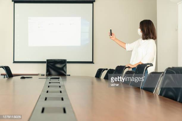 medicine face mask business woman presenting data on video screen - audience free event stock pictures, royalty-free photos & images